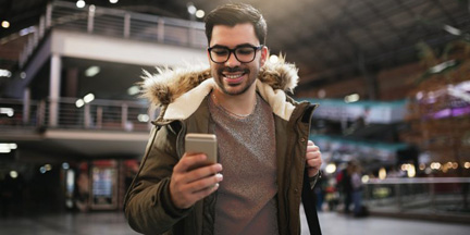 a young man wearing glasses and a backpack and holding a smart phone and smiling