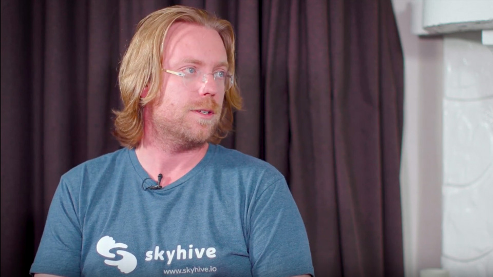 Sean Hinton wearing a skyhive t-shirt,                                  with his head turned to talk to his interviewer